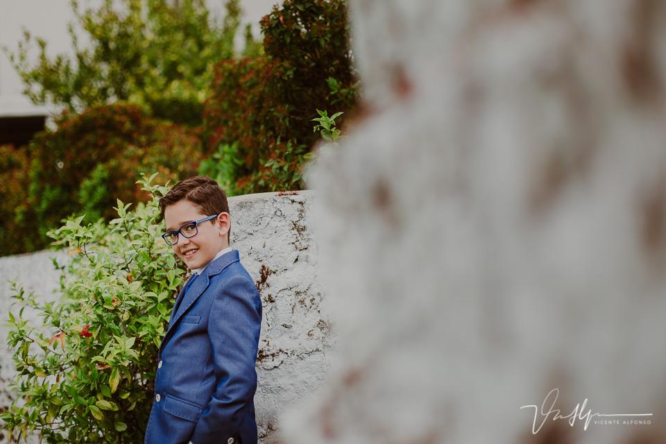 Niño apoyado en un muro de piedra en el reportaje de comunión