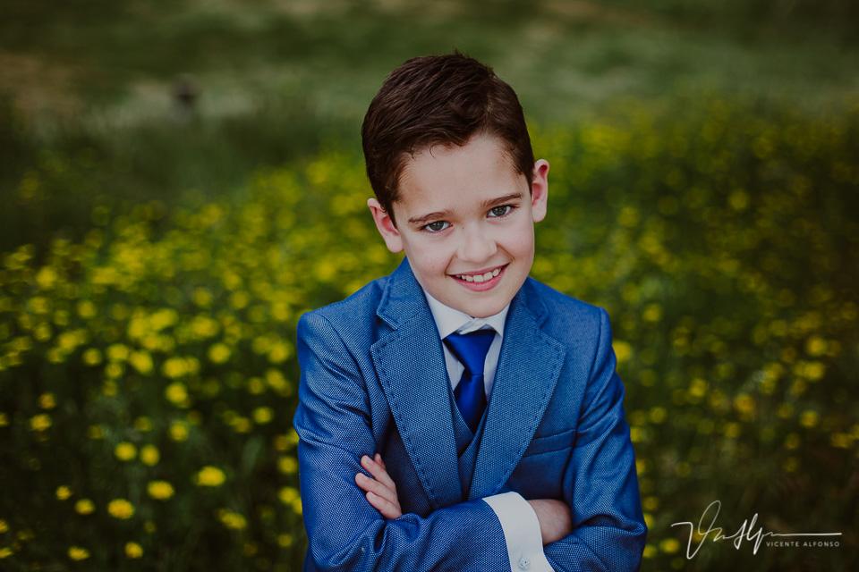 Retrato de niño de comunión junto a margaritas en exteriores