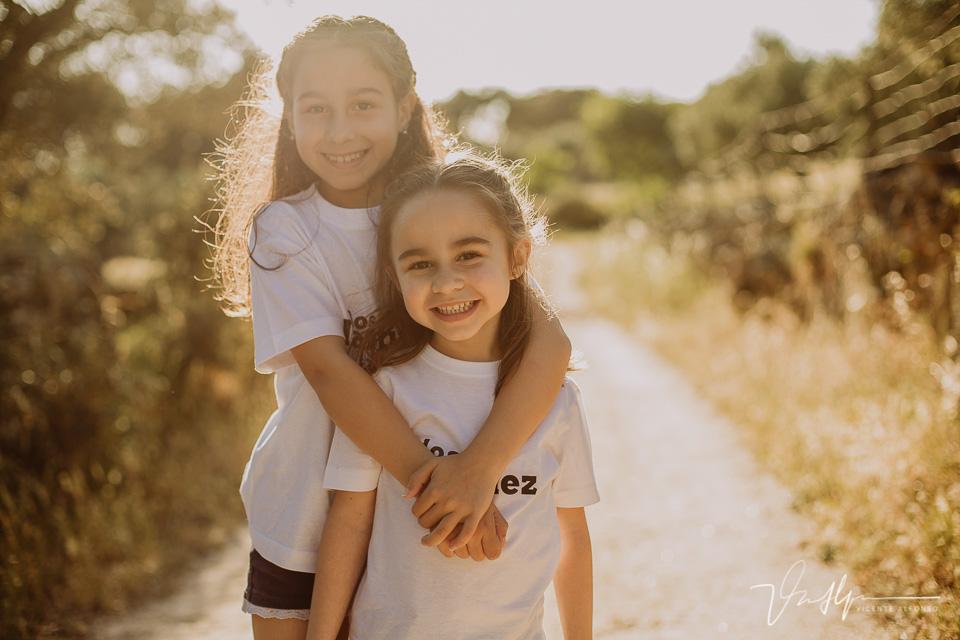 Hermanas abrazadas en el campo al atardecer