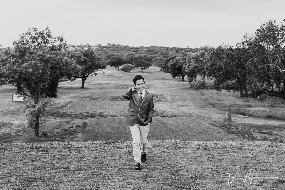 Niño vestido de comunión andando por el green en un campo de golf