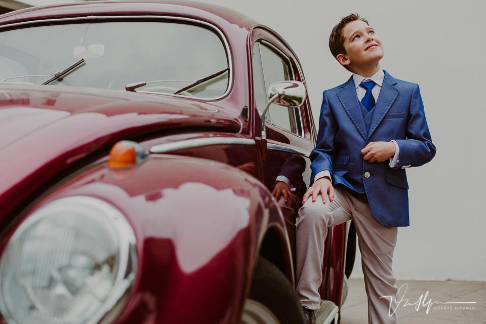 Niño de comunión apoyado en un coche clásico