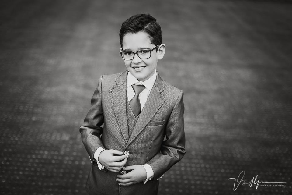 Retrato en blanco y negro de un niño vestido de comunión con traje y corbata