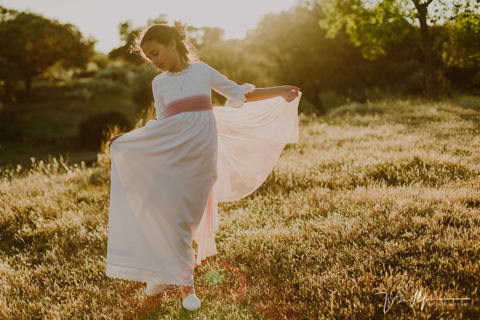 Niña bailando con vestido de comunión al atardecer en el campo