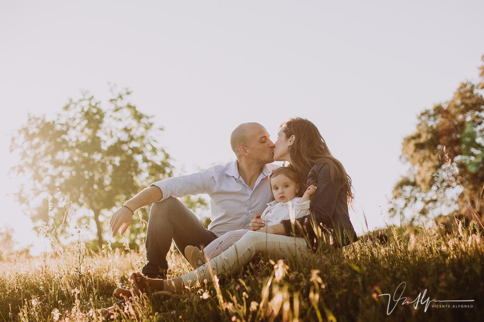 Familia besándose con su hija en el campo
