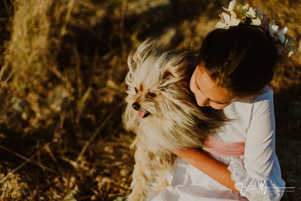 Niña de comunión jugando con su perrito en el campo