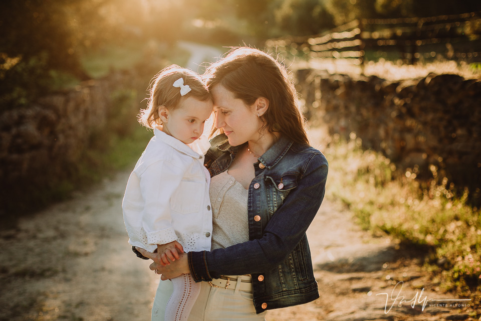 Madre abrazada a su hija pequeña en el campo