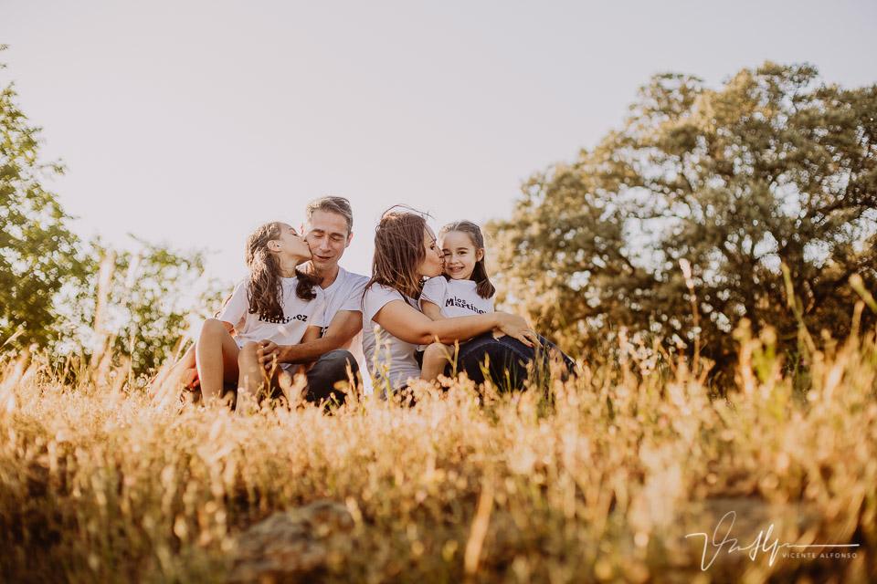 Familia sentada y abrazada en el campo al atardecer