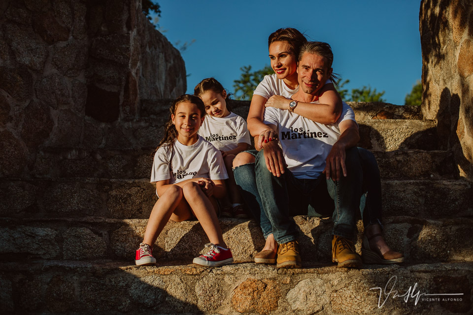 Familia de 4 personas sonriendo en unas escaleras en ruinas