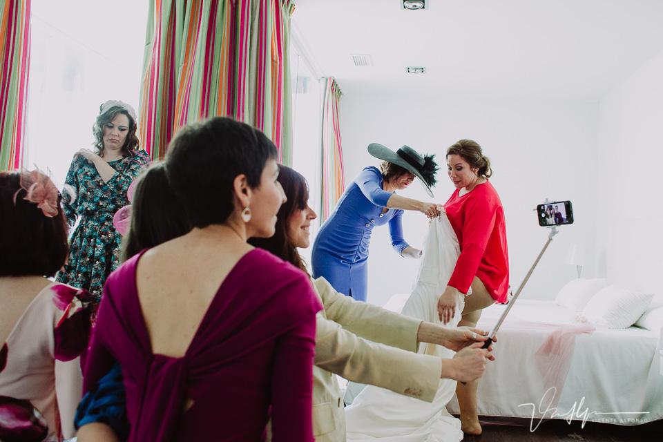 Las amigas de la novia haciendo un slefie mientras se viste la novia