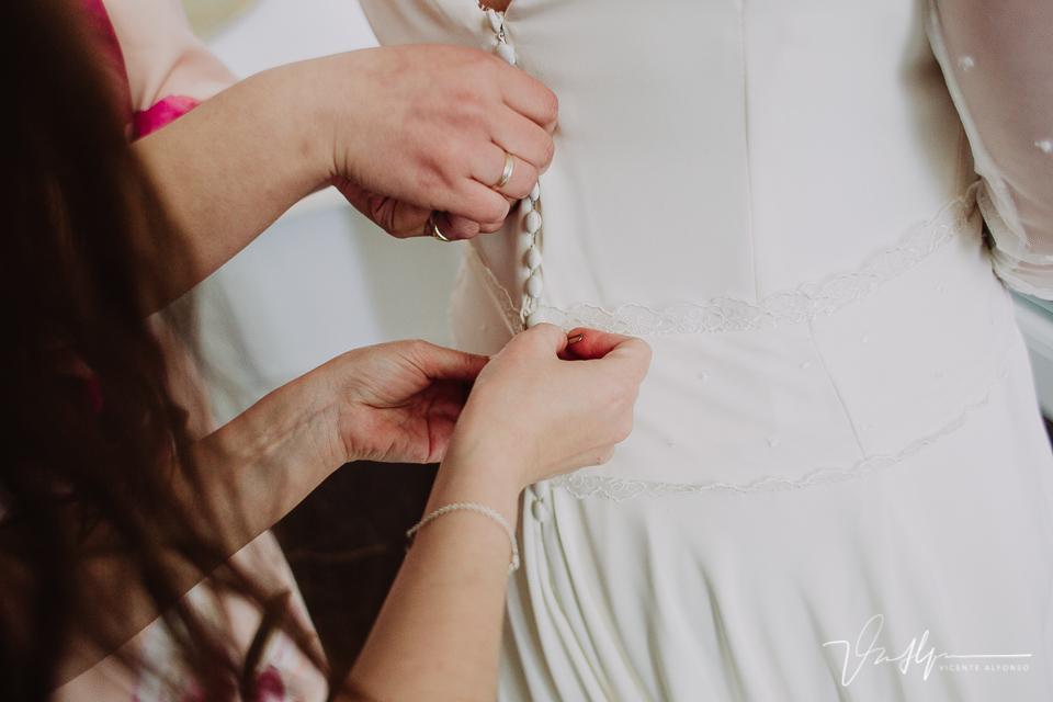 Uniendo los botones del vestido de novia