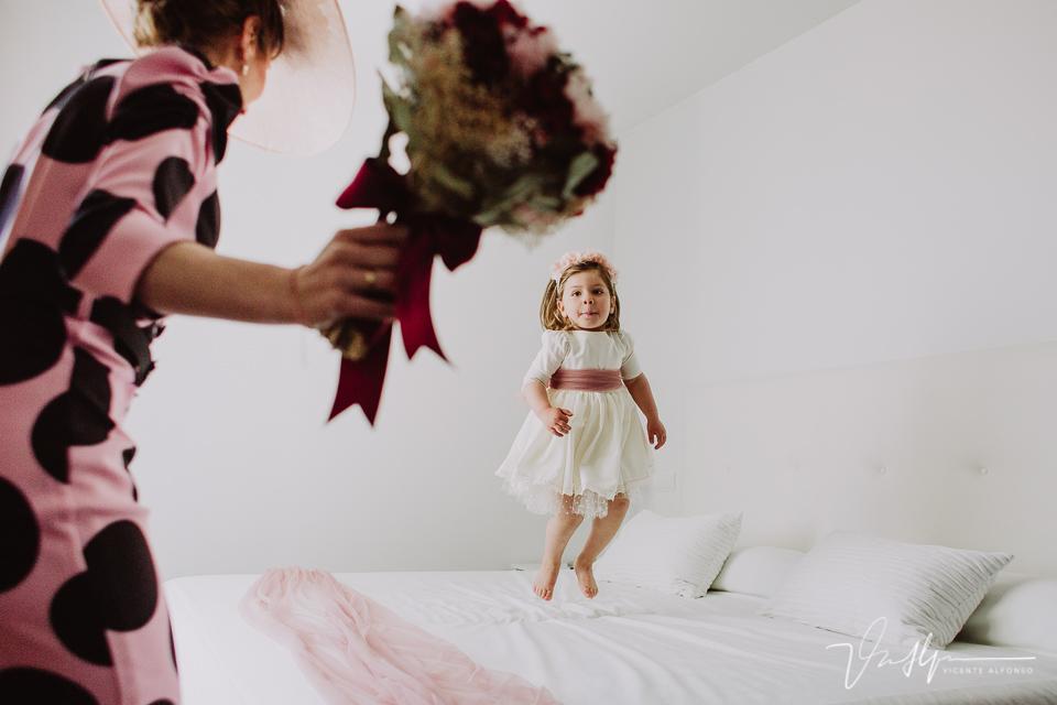 La hija de la novia saltando en la cama junto al ramo de flores