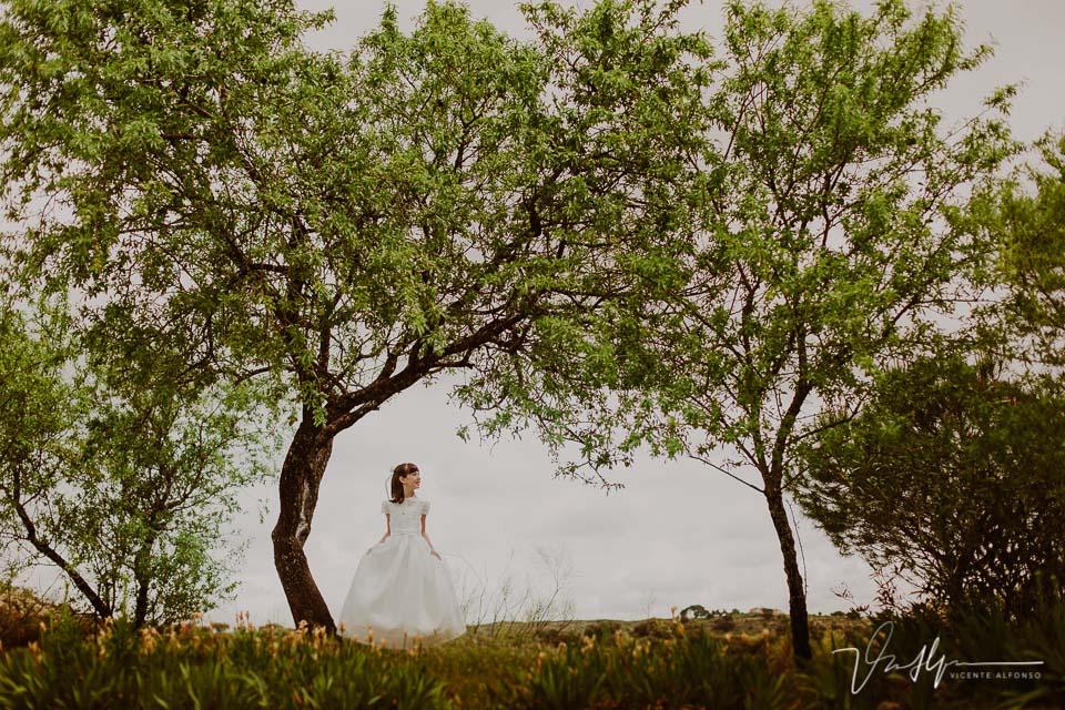 Niña vestida de comunión en exteriores entre árboles