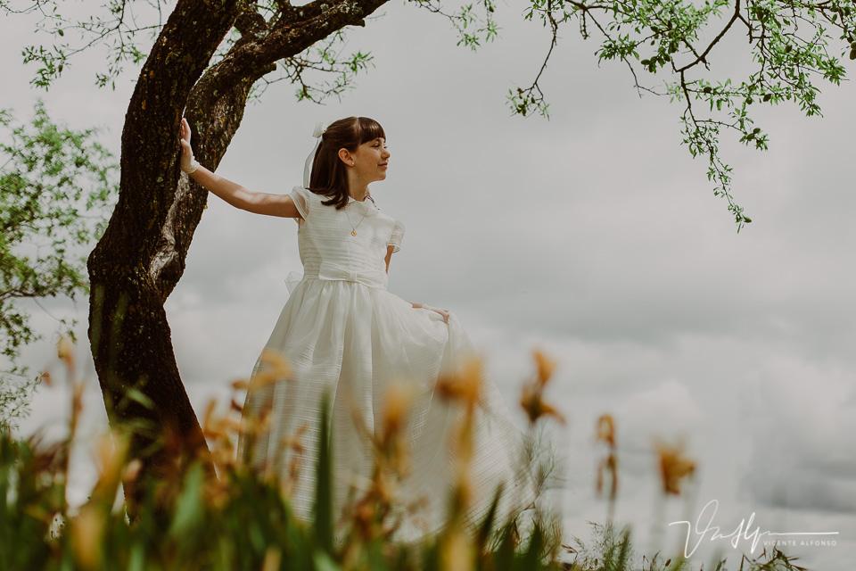 Niña apoyada sobre tronco con vestido de comunión