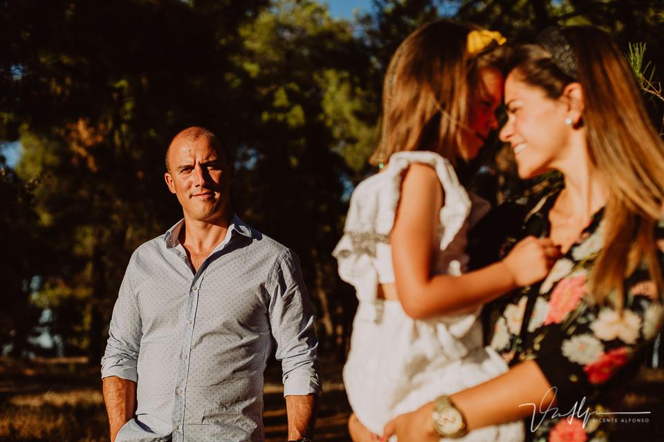 Padre mirando a cámara mientras hija y madre se abrazan