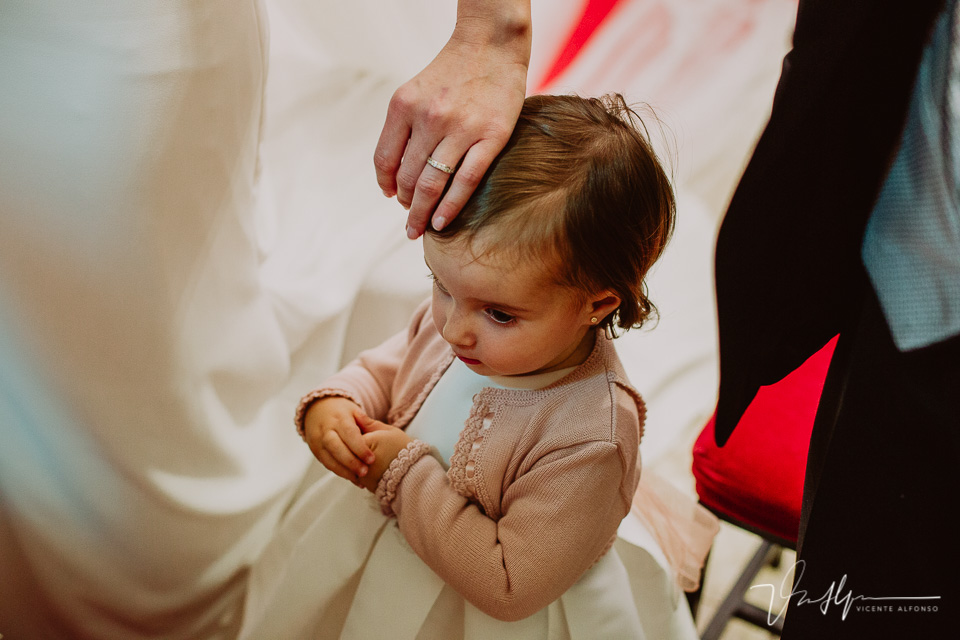 tocando la cabeza de su hija