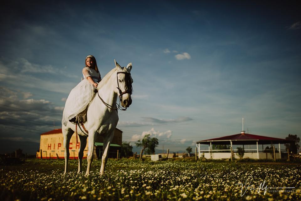 Niña sobre un caballo de comunión