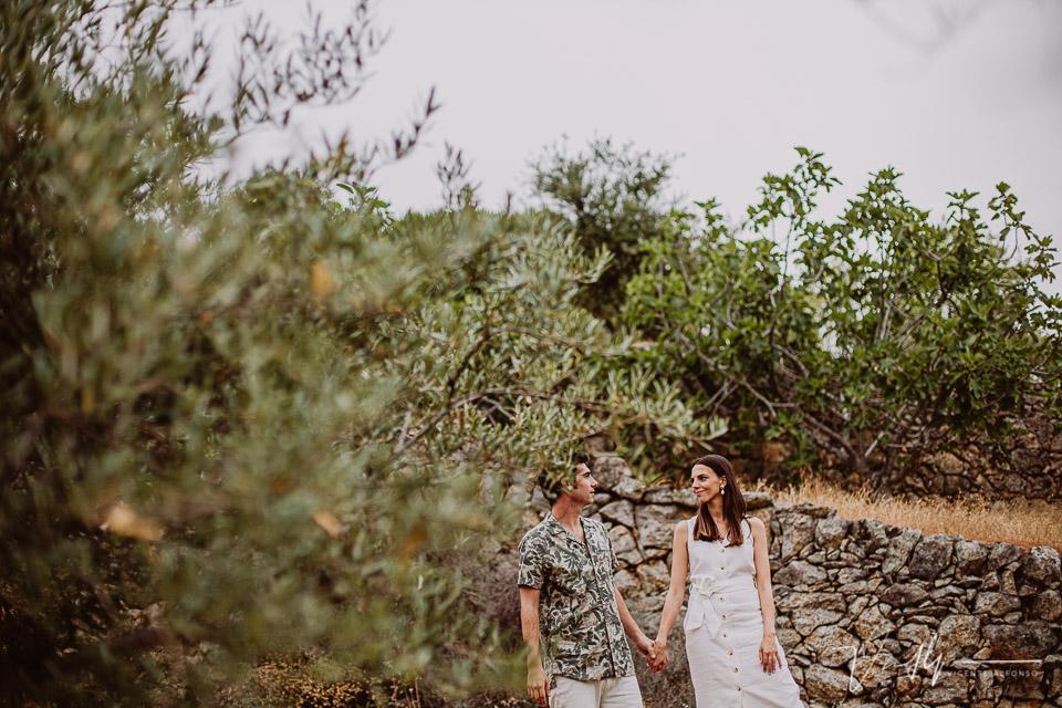 Pareja entre muros de piedra y olivos