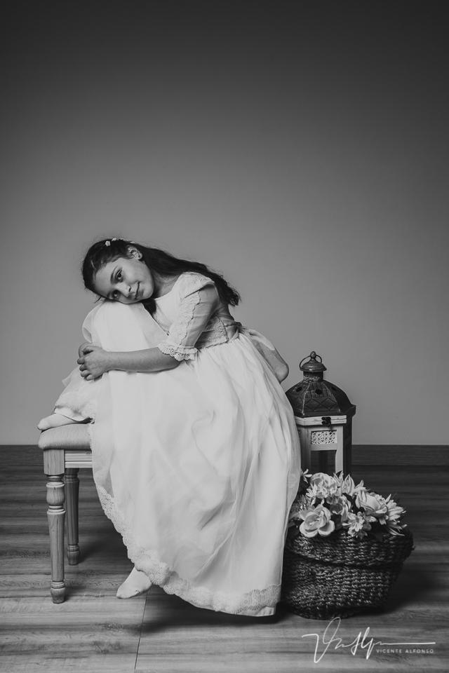 Niña vestida de comunión sentada en estudio
