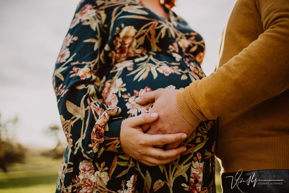 Manos juntas encima de la barriga de embarazada